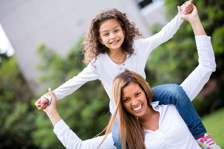 shoulder ride: Happy mother and daughter having fun at the park Stock Photo