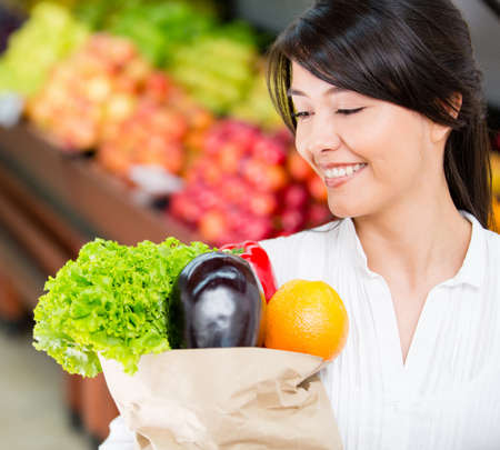 Latin woman grocery shopping looking very happy Stock Photo - 16717276