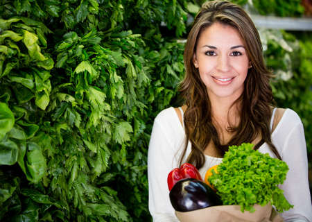 Healthy woman buying fresh vegetables at the supermarket photo