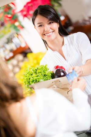 mercearia: Mulher pagando com cart�o de cr�dito no check-out Banco de Imagens