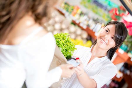 people buying: Woman paying at the supermarket with credit card Stock Photo