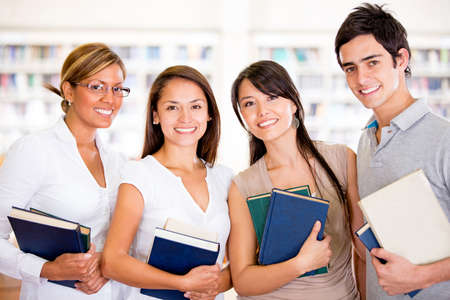 librarians: Group of university students holding books and smiling Stock Photo