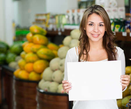 Woman with an open sign at her grocery business photo
