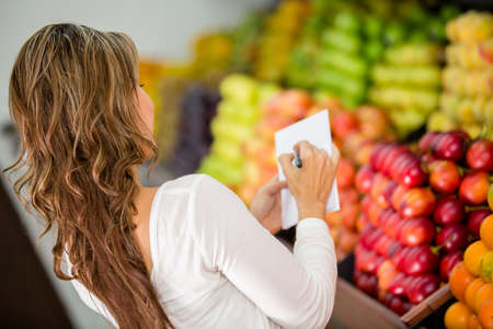 grocery shopping: Woman with a shopping list at the grocery store