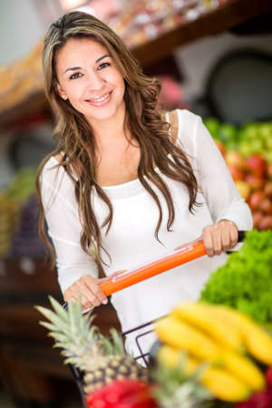 Woman at the supermarket buying groceries and looking happy photo