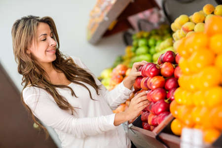 Woman buying fresh fruits at the supermarket photo