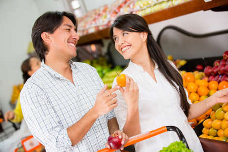 Happy couple grocery shopping at the local market Stock Photo - 16711141