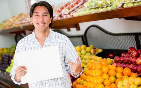 abarrotes: Hombre con una muestra abierta en su negocio de abarrotes Foto de archivo