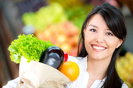 Woman grocery shopping and looking very happy photo