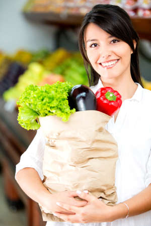 Female shopper holding a paper bag with groceries photo