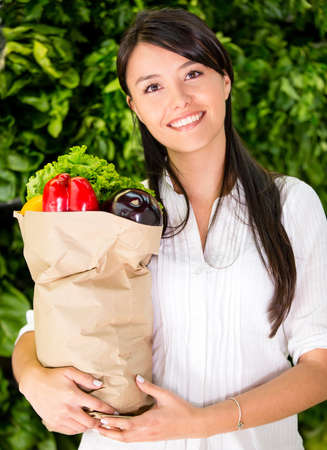 Healthy woman buying fresh food at the local market photo