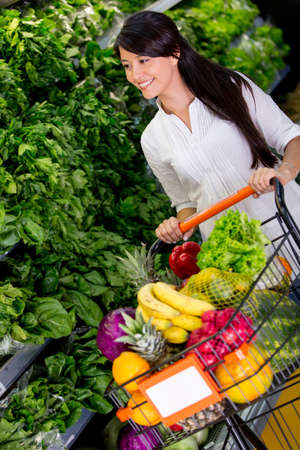 Woman shopping organic groceries at the supermarket photo