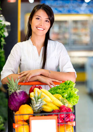 Woman at the supermarket with a shopping cart full of groceries Stock Photo - 16711089