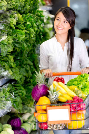 shoppers: Casual woman grocery shopping at the supermarket
