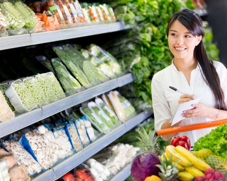 shopping list: Woman at the supermarket with a shopping list