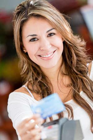pagando: Mujer comprador paga con tarjeta de cr�dito en una tienda