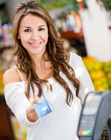 checkout: Woman at the checkout paying by credit card Stock Photo
