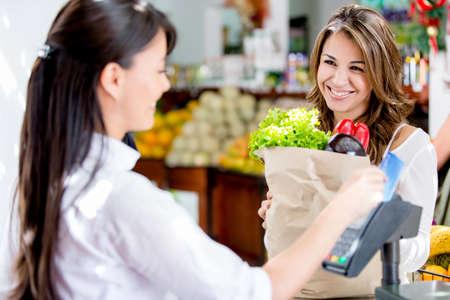 pagando: Mujer en la salida del mercado local paga con tarjeta de d�bito Foto de archivo