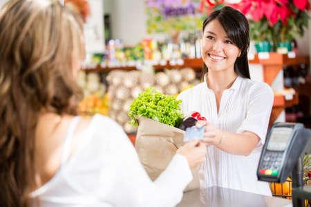 mercearia: Mulher da compra no caixa pagar com cart�o