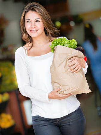 Happy woman shopping carrying a bag with groceries photo