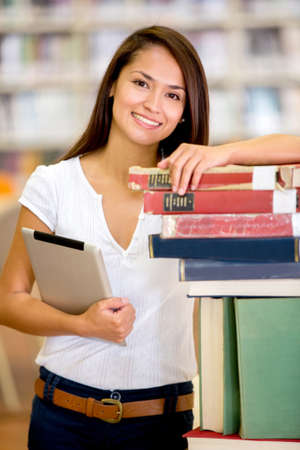 Female student at the library holding a tablet computer Stock Photo - 16711126