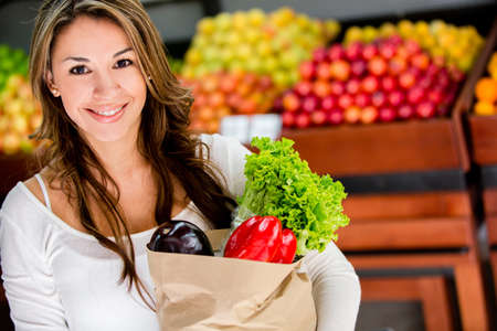 grocery shopper: Happy woman at the local market buying groceries
