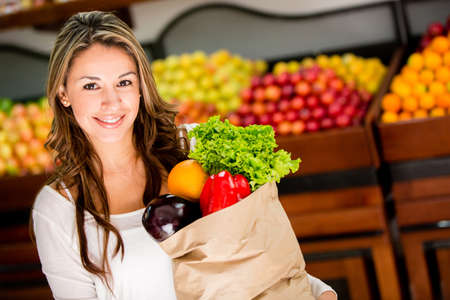 grocery shopping: Casual woman grocery shopping and looking happy Stock Photo