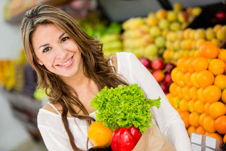 Happy woman at the supermarket buying groceries photo