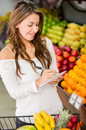 Woman with a shopping list at the local market photo