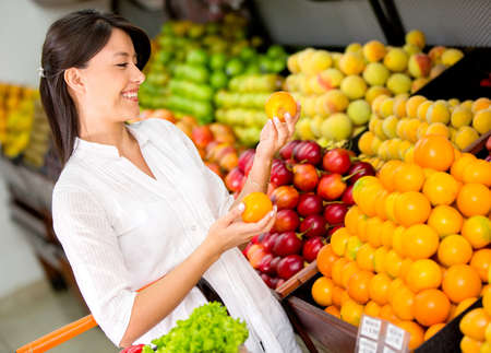 groceries: Mujer comprando fruta fresca en el supermercado