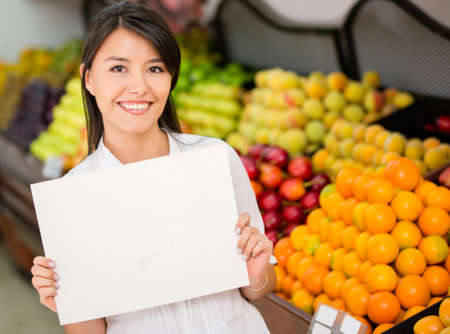 Female entrepreneur holding a banner at the supermarket photo