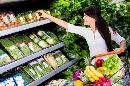 carro supermercado: Casual mujer de compras en el supermercado Foto de archivo