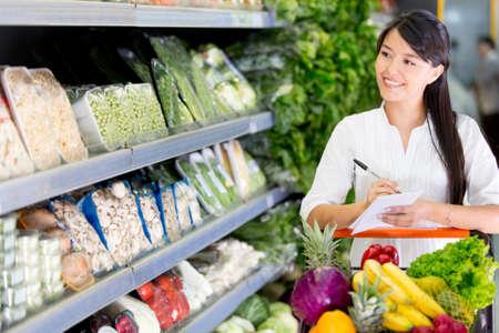 abarrotes: Mujer de compras con una lista en el mercado local