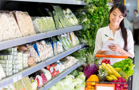 Woman with a shopping list for groceries at the market Stock Photo - 17425319