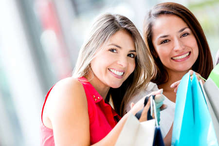 Happy shopping girls holding bags and smiling Stock Photo - 16763327