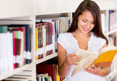 Female student at the library reading a book Stock Photo - 16802237