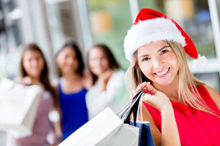Happy woman Christmas shopping wearing Santa hat photo