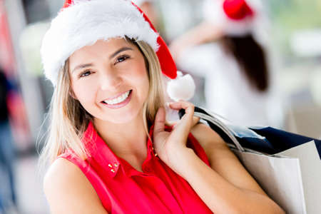 Happy woman shopping for Christmas and smiling photo