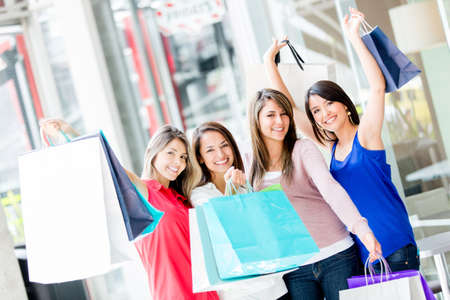 Happy group of shopping women with arms up photo