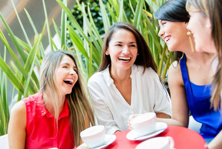Group of girls having a coffee and talking photo