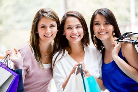 chicas comprando: Feliz grupo de amigas a comprar bolsas de tenencia