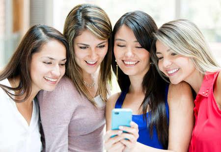 interaccion social: Grupo de chicas en busca de un tel�fono celular Foto de archivo