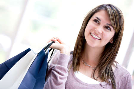 Pensive shopping woman looking up and holding bags Stock Photo - 16848456