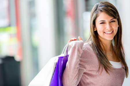 Happy shopping woman holding bags and smiling Stock Photo - 16848446