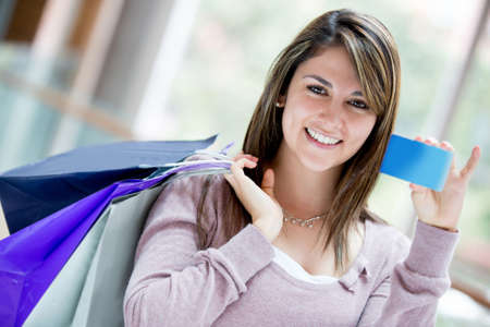 Happy female shopper holding a credit card and smiling Stock Photo - 16848464