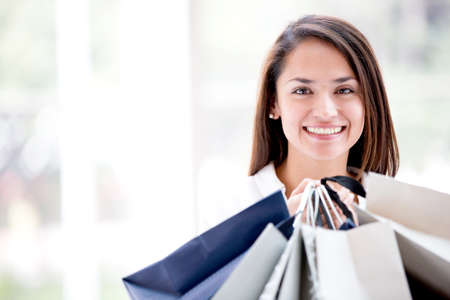 Latin woman holding shopping bags looking happy Stock Photo - 16848428