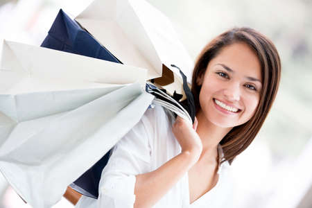 Happy woman holding shopping bags and smiling Stock Photo - 16848447