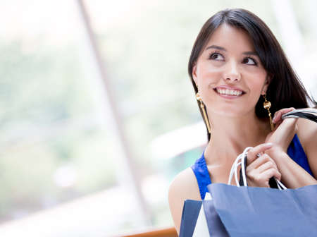 Thoughtful shopping woman holding bags and smiling photo