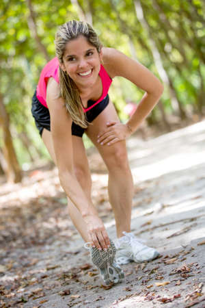 Fit woman exercising outdoors and stretching her legs photo