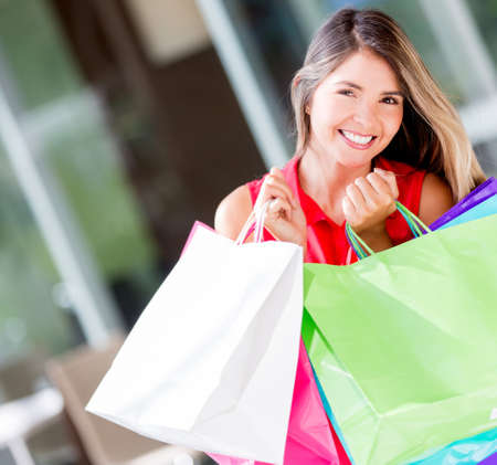 Happy female shopper holding shopping bags and smiling Stock Photo - 17482428